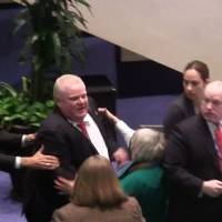 Stampede: Toronto Mayor Rob Ford knocks down Councilor Pam McConnell as he runs toward hecklers in the audience at City Hall on Monday.   AP