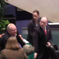 Stampede: Toronto Mayor Rob Ford knocks down Councilor Pam McConnell as he runs toward hecklers in the audience at City Hall on Monday. | AP