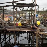 Starting over: A Filipino begins rebuilding his house in a waterfront community of Tacloban on Saturday. | AFP-JIJI