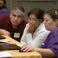 Keeping covered: Carlos and Martha Barajas look over their health insurance options with volunteer Elizabeth Lira (right) at a health fair in Sacramento, California, on Nov. 9. | AP