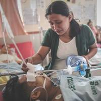 Ministering angel: A typhoon victim keeps her husband alive by pumping air into his lungs following a leg amputation that led to an infection at the Divine Word hospital, which still has no electrical power, Friday in Tacloban on the eastern Philippine island of Leyte | AFP-JIJI