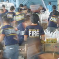 Aid action: Volunteers pack relief supplies for victims of Typhoon Haiyan at the Department of Social Welfare and Development in Manila on Saturday. | AFP-JIJI