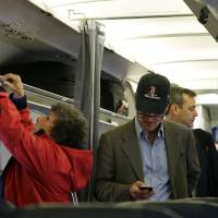 Pre-takeoff procedure: A passenger checks his cellphone for last-minute messages after boarding a flight in Boston. | AP