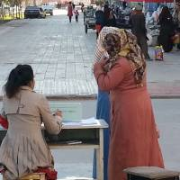 'Beauty' checkpoint: A Chinese government worker beckons two veil-wearing women to her stand on a street in Kashgar, in China's far-west Xinjiang region, on Nov. 9. | AFP-JIJI