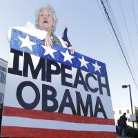 Unwelcome wagon: A woman holds a sign with other protesters while waiting for President Barack Obama to arrive at the Temple Emanu-El in Dallas on Nov. 6 | AP