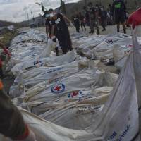 Grim duty: Filipino firefighters unload victims of Typhoon Haiyan outside Tacloban on Tuesday before forensic experts register and bury them in a mass grave. | AP
