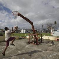 Play on: Michael Velasco, a survivor of Typhoon Haiyan, plays basketball on a damaged court at the Old Children's Park in the central Philippine city of Tacloban on Tuesday. Hundreds of thousands of people were displaced by the storm, which tore across several islands in the eastern Philippines on Nov. 8. | AP