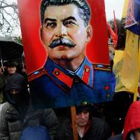 Sending a message: A man holds up a portrait of former Soviet dictator Josef Stalin as activists of various Russian nationalist movements take part in a rally during the National Unity Day in St. Petersburg on Nov. 4 | AFP-JIJI