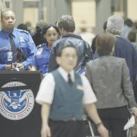 Terrorist or just tired?: TSA officials check passengers entering a security checkpoint at Atlanta's international airport. | AP