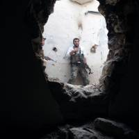 Call of duty: A rebel fighter holds a position in a damaged building during clashes with Syrian government forces in the northeastern city of Deir Ezzor on Monday | AFP-JIJI