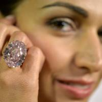 Shooting star: A Sotheby's employee shows the 'Pink Star' diamond, weighing 59.6 carats, during a preview at Sotheby's in Geneva on Sept. 25. | AP
