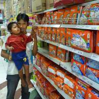 Growth market: A father and his son look for disposable paper diapers at a supermarket in Jakarta. Japanese diaper makers are banking on growing demand for their products in other Asian economies. | KYODO