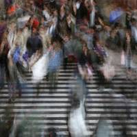 In a blur: Commuters cross a street in Tokyo. Japanese corporate earnings doubled last quarter, thanks to companies that made tough business decisions. | BLOOMBERG