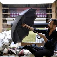 Luxury item: Frenchman Michel Heurtault, an umbrella and parasol artisan, displays one of his models at his Paris atelier in October. | AFP-JIJI