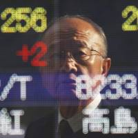 Speculation: A man is reflected in the window covering an electronic stock board at a securities firm in Tokyo on Thursday.   AP