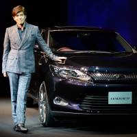 Targeting the young: Actor Koichi Sato stands beside Toyota's new Hybrid Harrier during a Wednesday press preview in Tokyo. | AFP-JIJI