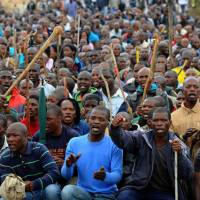 Striking out: Miners march during a strike over pay increases near the Marikana platinum mine in Marikana, South Africa, in September 2012. | AFP-JIJI