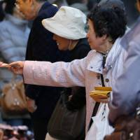 Legal tender: A woman pays a vendor at a market in the Ueno district of Tokyo in November. | BLOOMBERG