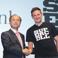 Superdeal: Masayoshi Son (left), chairman and chief executive officer of SoftBank Corp., and Ilkka Paananen, chief executive officer of Supercell Oy, hold a news conference Thursday in Tokyo | BLOOMBERG
