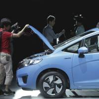 Fleeting milestone?: Reporters look at Honda Motor Co.'s new Fit Hybrid displayed at its launch in Urayasu, Chiba Prefecture, on Sept. 5.   BLOOMBERG