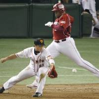 Split second: Tohoku Rakuten's Andruw Jones (rear) reaches first base before Yomiuri's Daisuke Nakai can make the catch in the 10th inning of the Golden Eagles 4-2 win on Thursday night. | KYODO