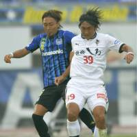 Going up: Gamba Osaka's Shu Kurata (left) tussles for the ball with Roasso Kumamoto's Hideaki Kitajima during Gamba's 4-0 win on Sunday. | KYODO