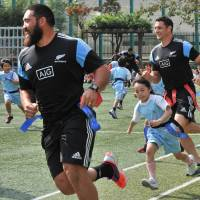 Child's play: All Blacks Charlie Faumuina (left) and Dan Carter take part in a touch rugby game with children during their visit to a Tokyo elementary school on Friday. | AFP-JIJI