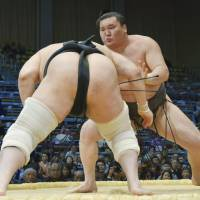 Another one bites the dust: Hakuho gets to grips with Aminishiki at the Kyushu Grand Sumo Tournament on Monday. | KYODO