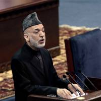 Troop talks: Afghan President Hamid Karzai speaks during the first day of the Loya Jirga in Kabul on Thursday. Karzai has told a gathering of elders that he supports signing a security deal with the United States if safety and security conditions are met. | AP