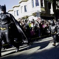 Next caper: Miles Scott, dressed as Batkid, runs with Batman after saving a woman in distress in San Francisco on Friday. | AP