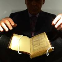 America's first book: A Sotheby's employee handles a copy of 1640's 'Bay Psalm Book,' the first book printed in what is now the United States, and considered the world's most valuable book, during an April preview at the auction house in New York. | AFP-JIJI