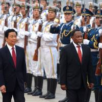 In step: Chinese Vice President Li Yuanchao and South African Deputy President Kgalema Motlanthe inspect a guard of honor during a welcoming ceremony outside the Great Hall of the People in Beijing on Oct. 28. China's economic relationship with Zambia is also growing quickly, spurring development but also friction | AFP-JIJI