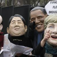 Looking for a deal: Climate activists spoof world leaders (from left) French President Francois Hollande, Prime Minister Shinzo Abe, U.S. President Barack Obama and German Chancellor Angela Merkel in front of the U.N. climate change conference at the National Stadium in Warsaw on Friday.   AP