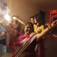Pyrotechnics: Indian Hindu women play with fireworks to celebrate Diwali, the Hindu festival of lights, in Allahabad on Sunday | AP