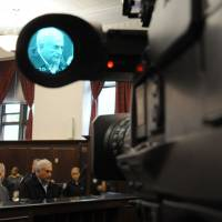 In the dock: IMF Director General Dominique Strauss-Kahn is seen through a video camera in Manhattan Criminal Court as he is arraigned on charges of attempted rape and criminal sexual contact in May 2011. The scandal is partly fueling a current debate in France about punishing clients of prostitutes. | AFP-JIJI