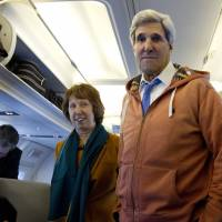 Wary negotiators: U.S. Secretary of State John Kerry and EU foreign policy chief Catherine Ashton visit the media seating area of Kerry's aircraft as it sits on the tarmac at Geneva International airport before leaving for London on Sunday in Geneva. | AP