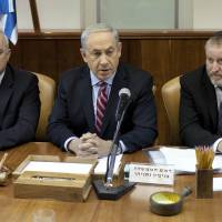 Not sold: Israeli Prime Minister Benjamin Netanyahu (center) speaks near Israeli Cabinet Secretary Avichai Mandelblit (right) during the weekly Cabinet meeting Saturday at his office in Jerusalem. Netanyahu slammed a nuclear deal between Iran and world powers as a 'historic mistake,' his spokesman said. | AFP-JIJI