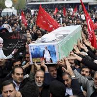 Funeral for adviser: Iranians carry the coffin of Ibrahim Ansari, Iran's cultural adviser in Beirut, after Friday prayers in Tehran. Ansari was a victim of a twin suicide bombing outside the Iranian Embassy in Beirut on Tuesday. | AP