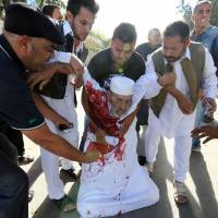 Shot down: People assist a man who was injured after Libyan militiamen opened fire on a crowd demanding the disbanding of the militia at the group's headquarters in southern Tripoli on Friday. | AFP-JIJI
