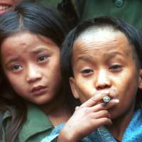 Band of rebels: Johnny Htoo (left), a 12-year-old Karen boy, watches his twin brother, Luther, smoke a cigar at their jungle base of Ka Mar Pa Law in Myanmar. The siblings, who grabbed headlines over a decade ago as 12-year-old twins leading a small band of anti-government guerrillas known as God's Army, were reunited in Thailand but have since traveled different paths. Luther moved to Sweden, while Johnny is living in a Thai refugee camp | AP