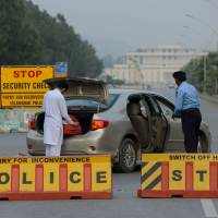 Hidden danger: A Pakistani policeman searches a car at a checkpoint on Constitution Avenue in Islamabad on Oct. 29 | AFP-JIJI