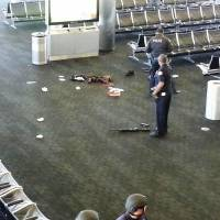 After the mayhem: Police officers stand near an unidentified weapon in Terminal 3 of Los Angeles International Airport on Friday. Officials said a gunman who opened fire in the terminal was wounded in a shootout with police and taken into custody   AP