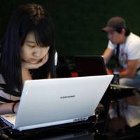 Anachronism: A South Korean woman tries out a laptop at Samsung Electronics' headquarters in Seoul in July 2010. South Korea is renowned for its digital innovation, but the tech-savvy nation is stuck in the past in one way: its slavish dependence on Internet Explorer | BLOOMBERG