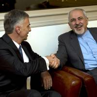 Breakthrough deal: Swiss Foreign Minister Didier Burkhalter (left) shakes hands with Iranian Foreign Minister Mohammad Javad Zarif during a meeting at the Intercontinental Hotel prior to talks about Tehran's nuclear program in Geneva on Saturday. | AP