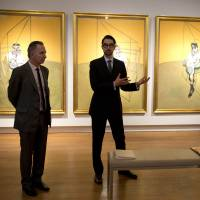 Cash cow: Spokesmen from Christie's auction house discuss Francis Bacon's 'Three Studies of Lucian Freud,' seen in the background, in New York. The work was sold for $142.4 million Tuesday, smashing the world record for the most expensive piece of art ever auctioned | AFP-JIJI