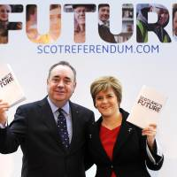 Pick and choose: Scottish First Minister Alex Salmond and Deputy First Minister Nicola Sturgeon pose for a picture during a news conference to launch their regional government's long-awaited white paper ahead of next year's historic independence referendum in Glasgow on Tuesday. An independent Scotland would keep Queen Elizabeth II as its monarch but create its own defense force, nationalist leader Salmond said as he unveiled the detailed proposals. | AFP-JIJI