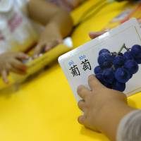Fruitful: A child holds a flashcard during a Chinese lesson at the TEO kindergarten in Madrid. Its director said the facility launched after-hours Chinese lessons after many other schools in Madrid started doing so, as Spaniards look to China's fast-growing economy for opportunities following five years of recession at home | AFP-JIJI