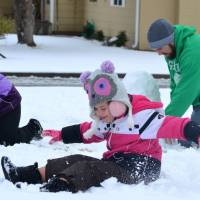 Let it snow: Audree Todd (left) gathers up a snowball to toss at her sister, Kensie, during a snowman-building session with their father, Casey, at their home in Lawton, Oklahoma, on Sunday. | AP