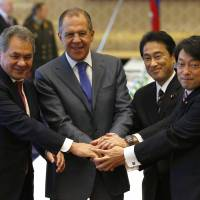 Show of hands: Foreign Minister Fumio Kishida (second from right) and Defense Minister Itsunori Onodera pose for a group shot with their Russian counterparts, Sergey Lavrov (second from left) and Sergei Shoigu, at the start of their 'two-plus-two' meeting in Tokyo on Saturday morning | AP