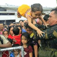 Out of order: Philippine military personnel prioritize women and children as people wait for evacuation flights out of the typhoon-stricken Philippine city of Tacloban on Tuesday   AP